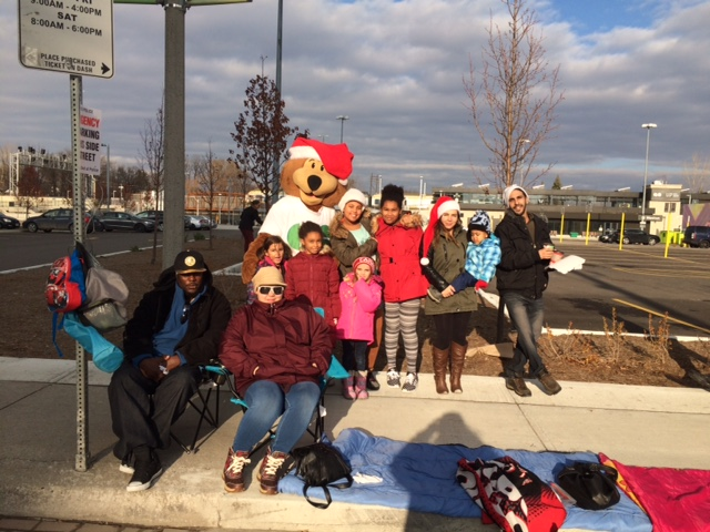 Those watching the Santa Claus parade pose with GO Bear, along the route.
