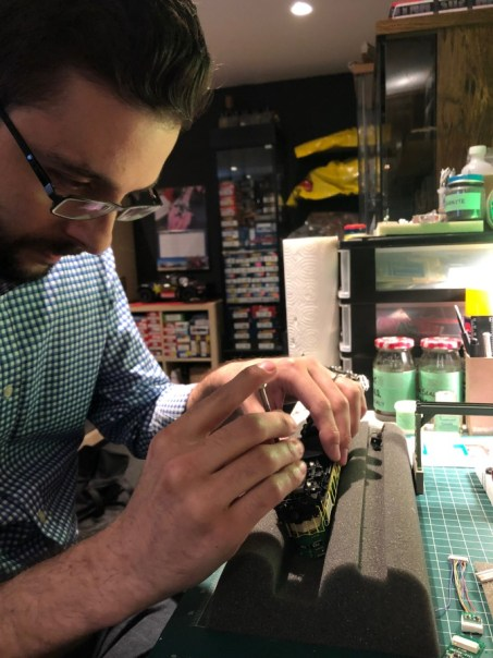 Chris Balestri works on a model train with a small screwdriver.