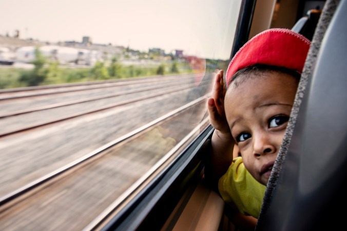 A child looks out the window of the UP train.