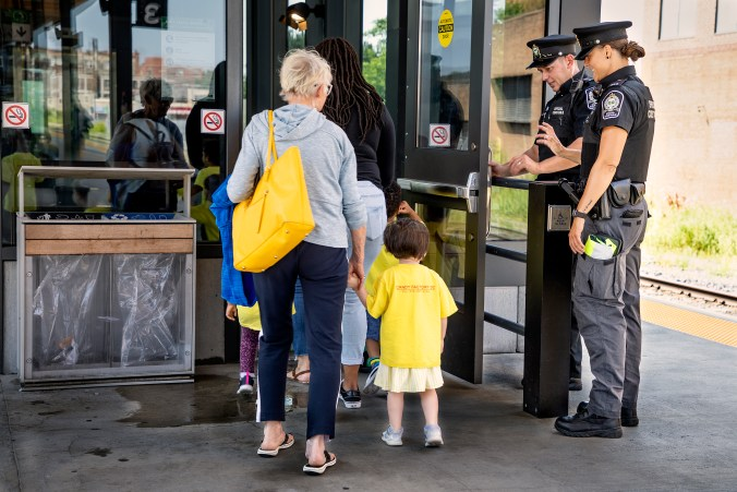 Children wave at transit safety officers as they leave the platform, on the way home.