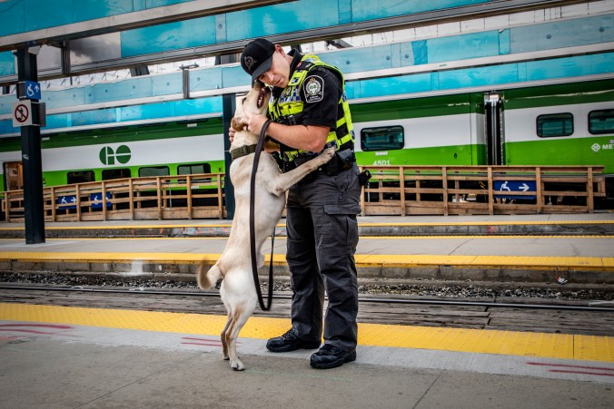 Dash jumps up to lick Officer Hoffman.