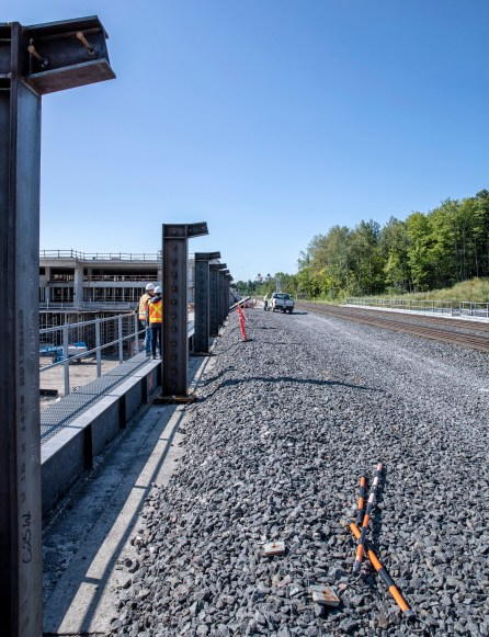 A gravel bed supports rails, as workmen toil nearby.