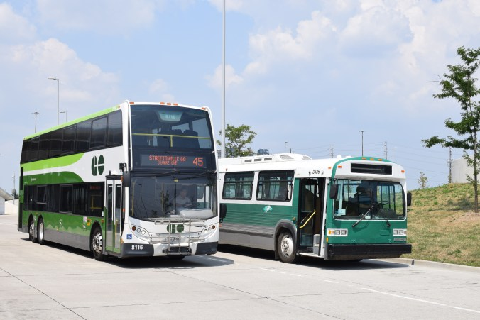 A picture of a double decker GO bus and the 1990 MCI Classic bus side by side