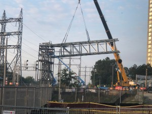 A large piece of metal structure is lifted by a crane into place.