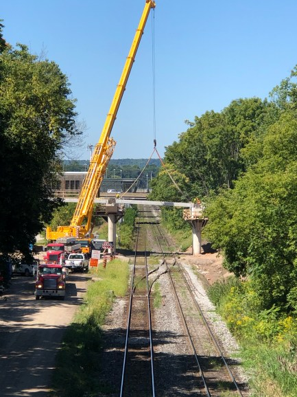 A massive crane lifts a piece of bridge into place near Hamilton's West Harbour GO Station