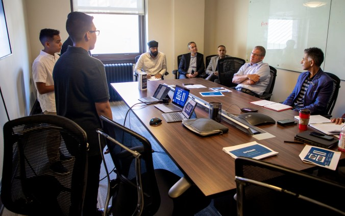 Three young men stand in a board room and share their ideas with a panel of Metrolinx experts.