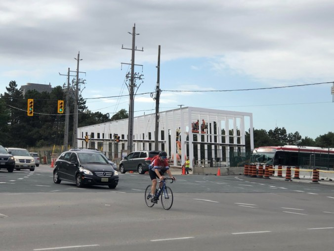 A man rides a bike through the intersection.