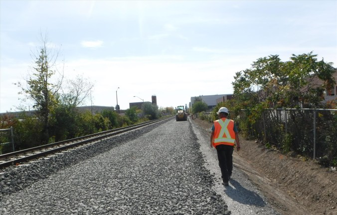 A man walks alongside of the new rail.