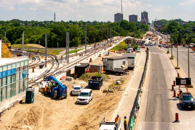 Image shows work being done on the elevated guideway, next to a busy roadway.