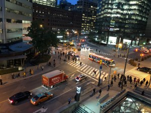 Scene shows a crowded downtown intersection.