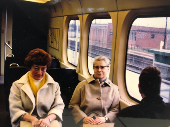Two women sit next to a man on a GO train.