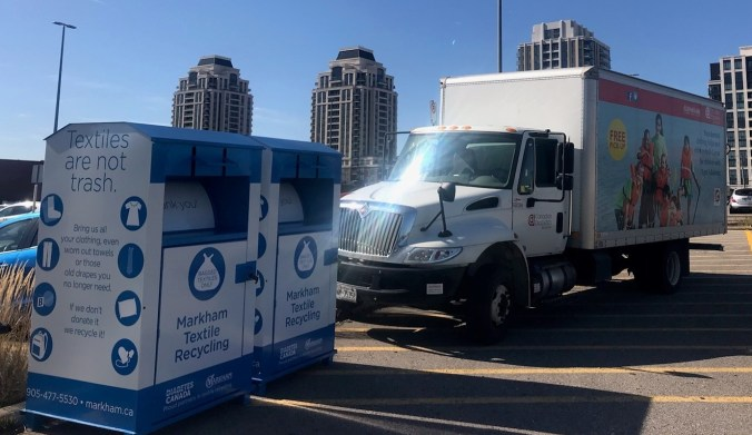 A donations truck is seen parked by two bins.