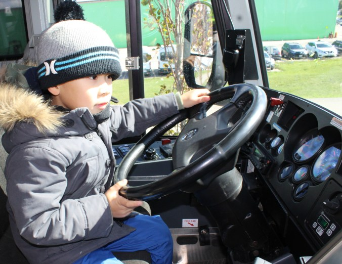 A young child steers the wheel of the GO bus.