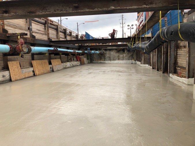 Photo of a large hole in the ground below Eglinton where concrete has been poured into a smooth slab that will make up the roof of the underground station.