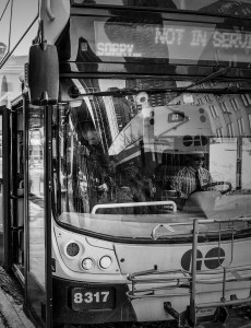 A passenger is seen stepping off of a GO bus on a cold day.