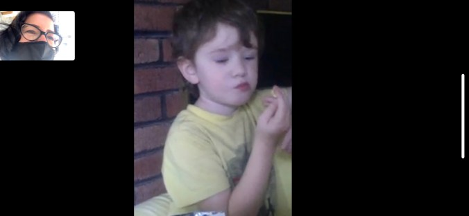 A child eats popcorn while on a virtual meeting