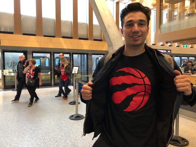 A customer shows his Raptor's shirt, while standing at the UP Express platform.