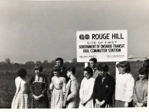 Students stand in front of a large sign promoting the Rouge Hill site.