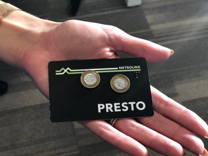 A PRESTO card and TTC tokens on a person's hand.
