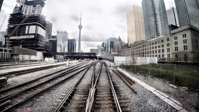 Empty tracks are shown against the cityscape of Toronto.