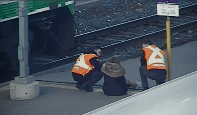 Two staff members talk to a young woman on a train platform.