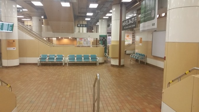 Image shows the old, brown tiles and green seats of the Old Bay Concourse.