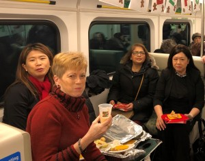 Customers eat a meal and smile at the camera on a GO train.