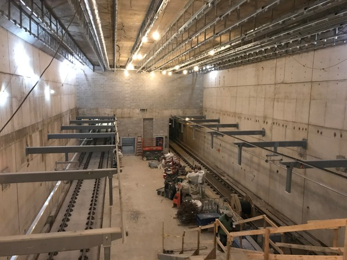 Show the concrete inside of the sttaion, with tracks on two sides of a very large room.