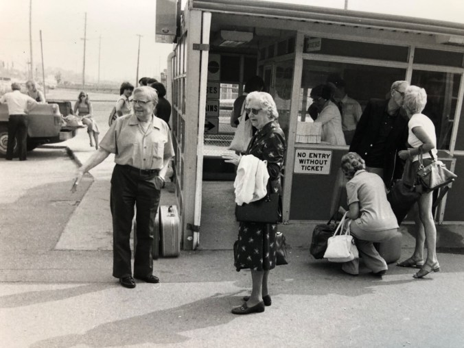 A group of customers stand outside the ticket booth.