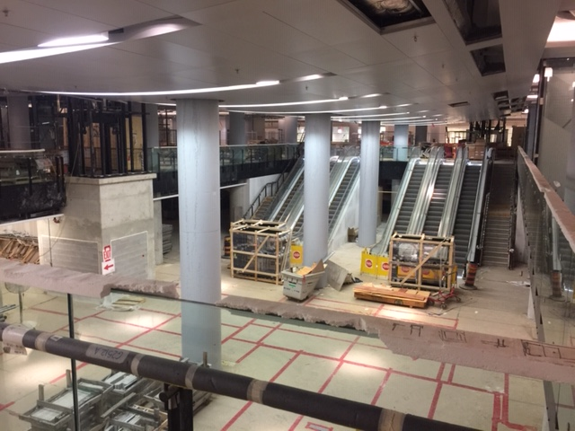 Image shows escalators installed, as the floor remains covered during construction.
