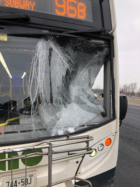 Image shows a bus with badly shattered windshield.