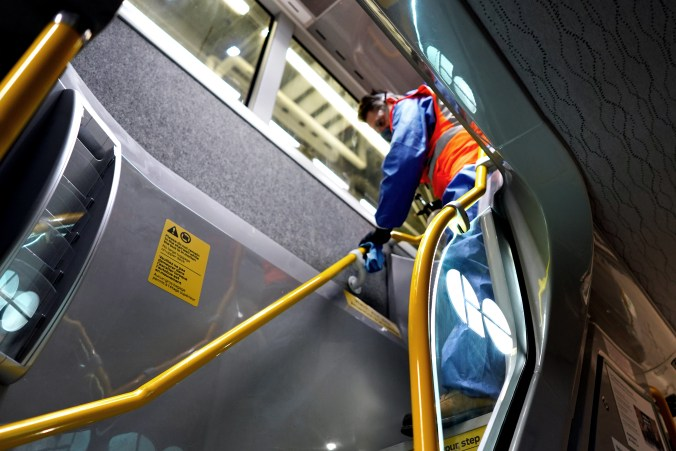 A cleaner polishes the rail of steps leadin to the second floor of a GO train.