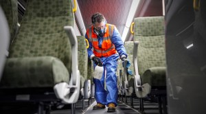 A man wipes down GO bus seats.