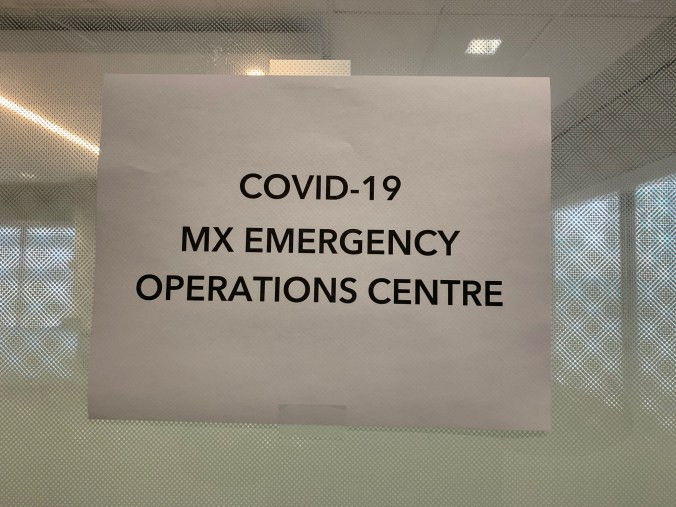 A sign at the entrance to the command centre reads 'COVID-19 MX Emergency Operations Centre