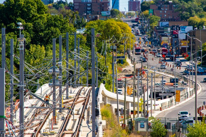 Image shows a spiderweb of wires above tracks.