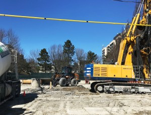 Construction machinery like excavators work on a Finch West LRT work site