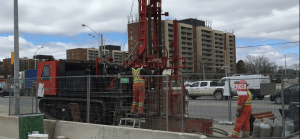 Construction workers using a large drill rig to drill holes in the ground near Finch and Keele