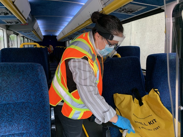 A cleaning person disinfects a GO bus