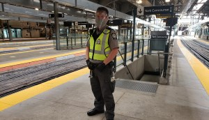 Fare inspector standing on GO platform decked out in new safety gear