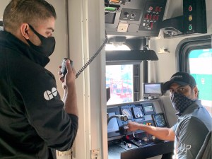 Two Merolinx employees go about their day on UP Express, while wearing face coverings. (Anne Marie Aikins photo)