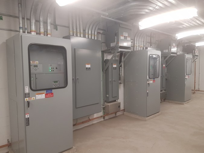 Image shows electrical boxes inside a large room.