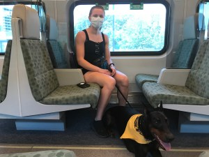 Woman named Olivera Krolj sitting on GO train in a mask, with her dog