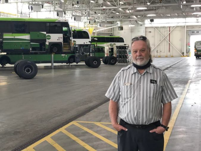 GO Bus driver stands in the garage with buses int he background