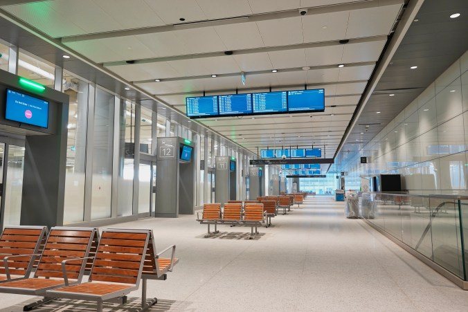 shot of the interior of the new bus terminal showing benches, escalators, departure gates and sceens