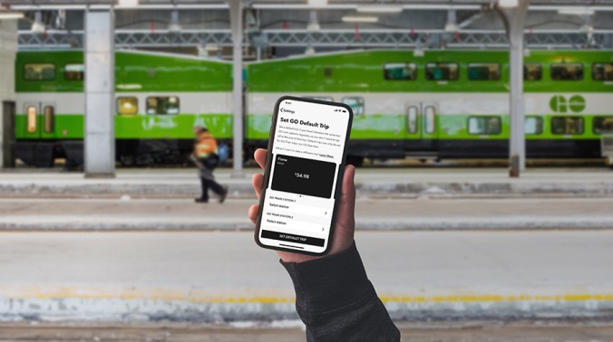 A hand holds up a phone with the PRESTO app on it.