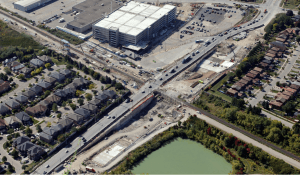 Image is a drone shot of the local community and parking garage.