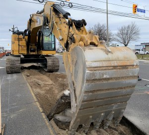 Images shows a tractor digging into the ground.