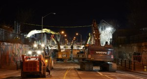 Tractors and crews work on taking down the pedestrian bridge at night.