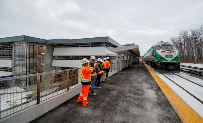 A GO train pulls slowly in as staff stand on the platform.