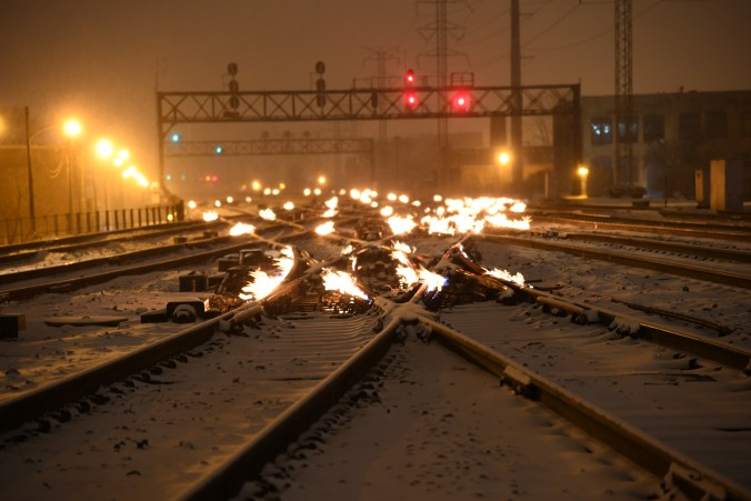 view of the tracks at night in winter, with gas fired flames on to keep switches clear in Chicago